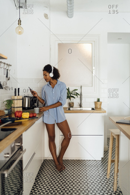 Woman with headphones- using smartphone and drinking coffee for breakfast in her kitchen