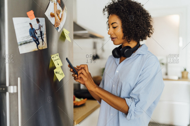 Woman in her kitchen in the morning- posting sticky  notes on the fridge