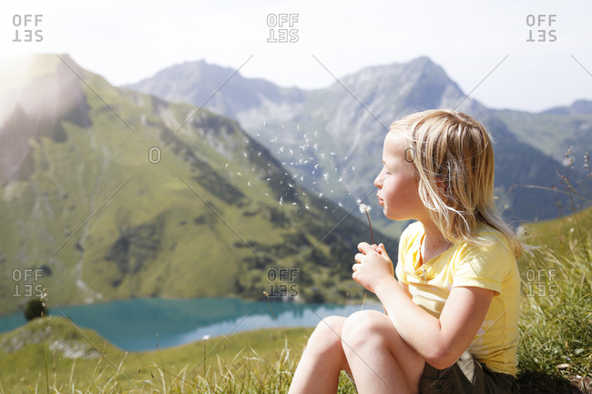 Austria- South Tyrol- young blond girl blowing blowball