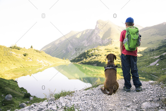 Austria- South Tyrol- young boy standing next to his dog