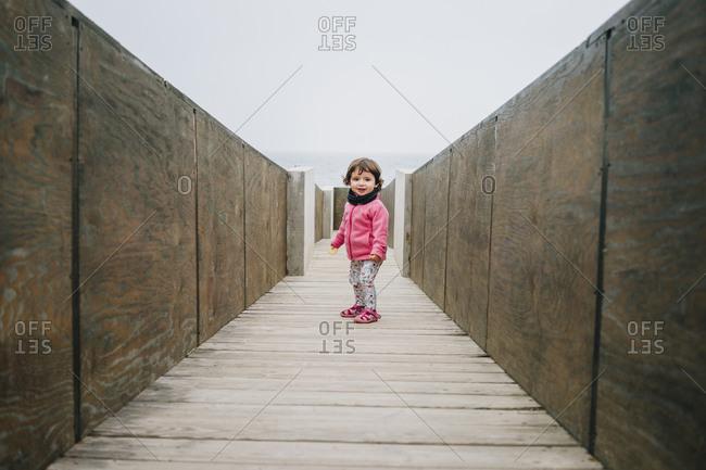 Baby girl walking on a wooden walkway