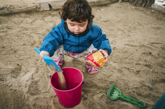 Baby girl playing with sand- shovel and bucket
