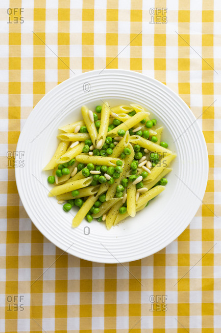 Penne with peas and pine nuts on plate- from above