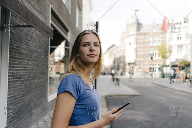 Netherlands- Maastricht- smiling young woman with cell phone in the city looking around