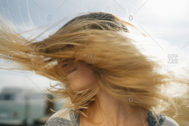 Blonde young woman at camper van shaking her hair