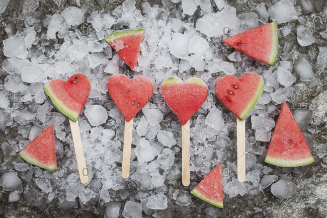 Watermelon heart ice lollies on crashed ice