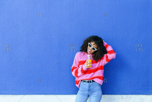 Portrait of smiling young woman with bottle of orange juice standing in front of blue wall