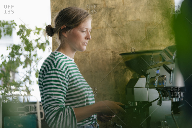 Young woman preparing coffee in a cafe