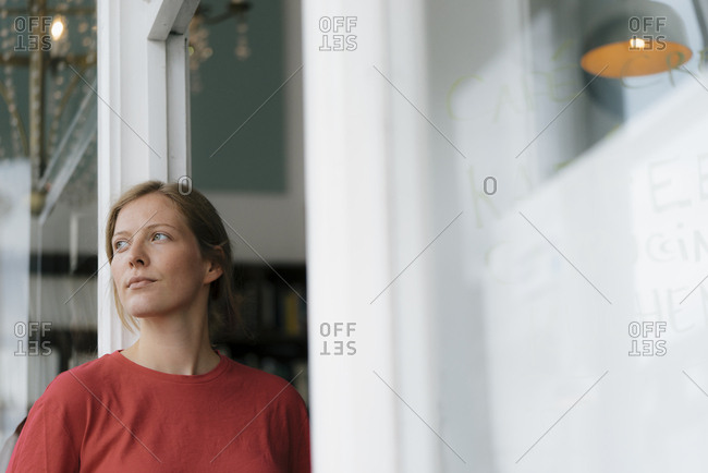 Young woman at French door in a cafe looking around