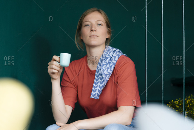Young woman sitting in a cafe holding espresso cup