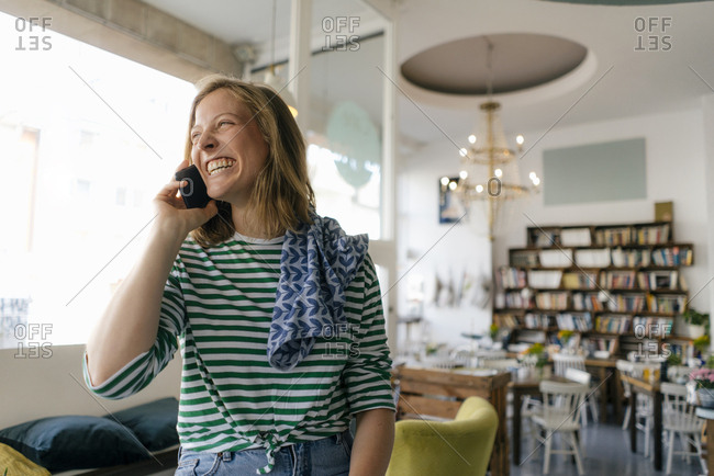 Laughing young woman on cell phone in a cafe