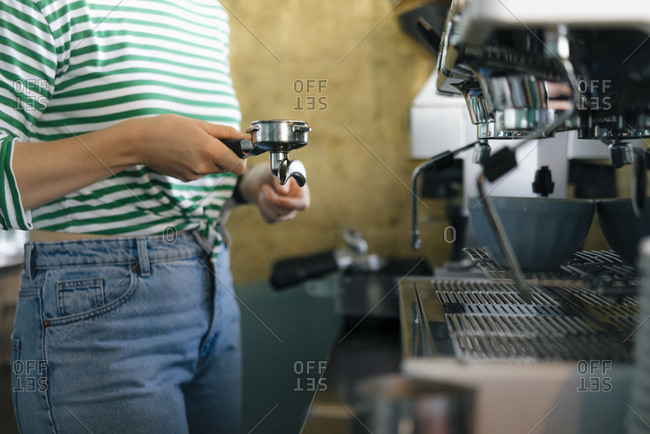 Close-up of young woman preparing coffee in a cafe