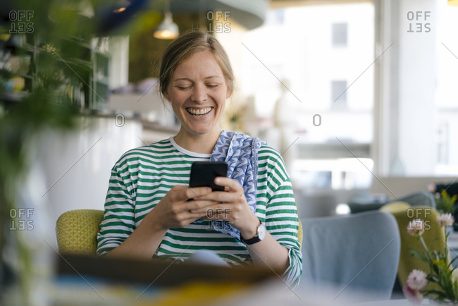 Laughing young woman looking on cell phone in a cafe
