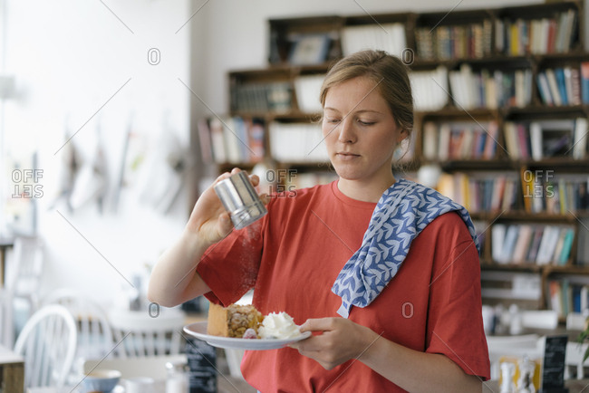 Young woman serving plate with cake in a cafe