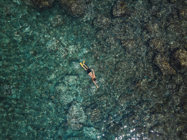 Indonesia- Bali- Man swimming in ocean at Amed beach