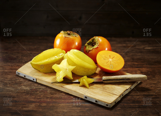 Whole and sliced Kakis and star fruits on wooden board