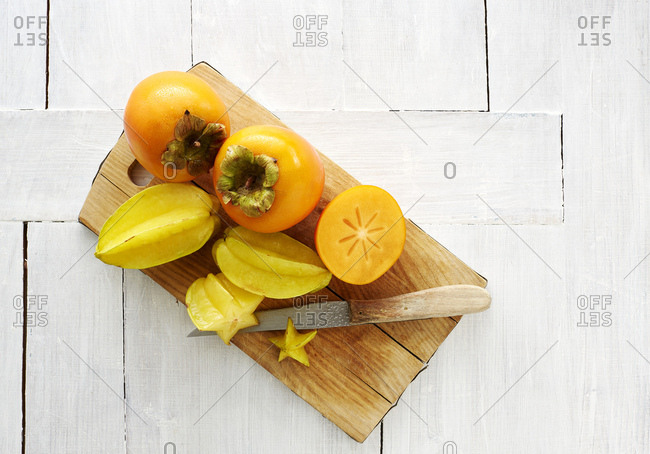 Whole and slices Kakis and star fruits on wooden board