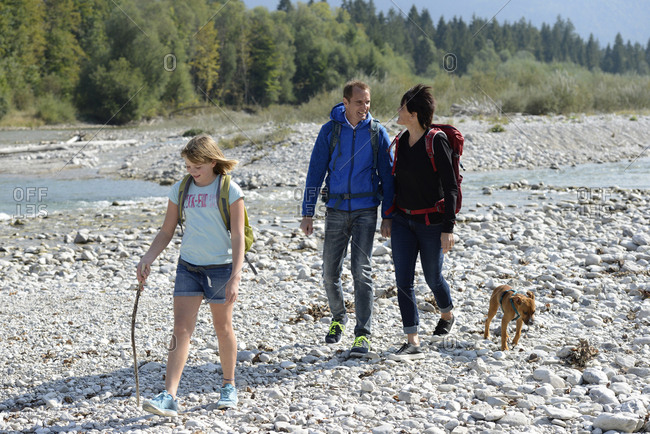 Family hiking with backpacks and a dog at the river Isar- Upper Bavaria- Germany
