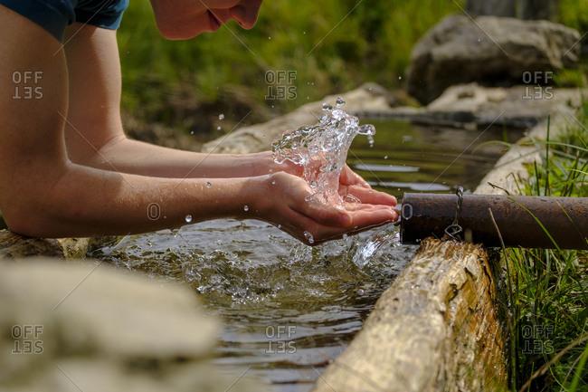 Germany- Upper Bavaria- Chiemgau- Young man refreshing at a fountain