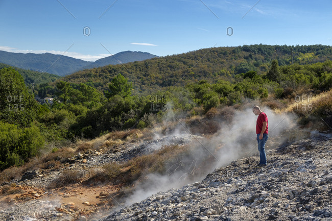 Italy- Tuscany- Colline Metallifere- Val di Cecina- Sasso Pisano- Valle delle Diavolo- hiker looking at geothermal field