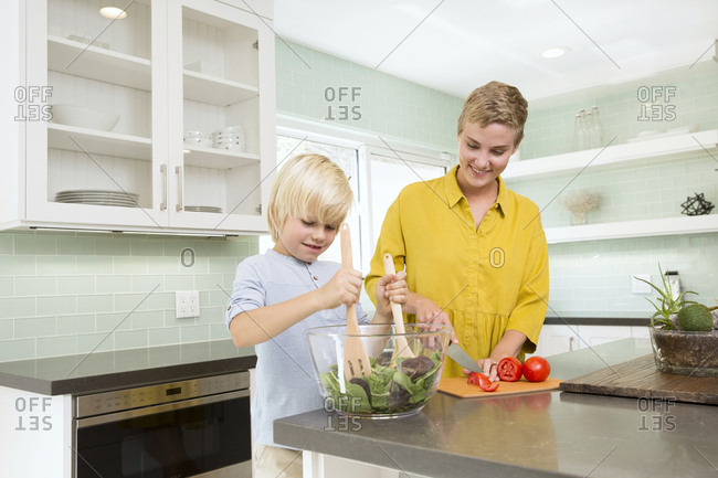 Smiling mother and son preparing salad in kitchen together
