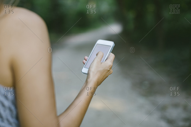 Woman using smartphone on forest track- partial view