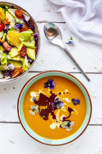 Bowl of mixed salad with edible flowers and bowl of creamed pumpkin soup garnished with edible flowers