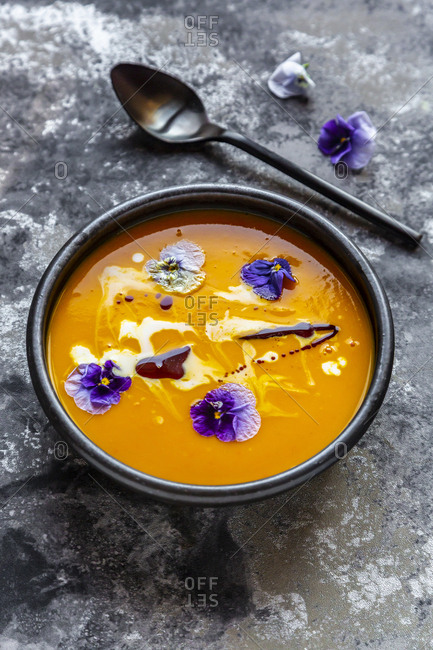 Bowl of creamed pumpkin soup garnished with edible flowers