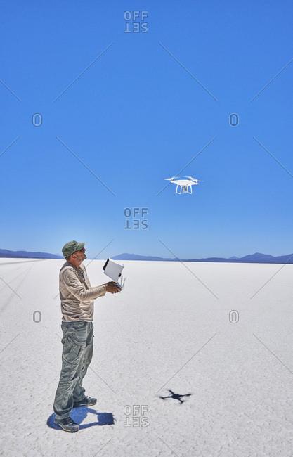 Bolivia- Salar de Uyuni- man flying drone on salt lake