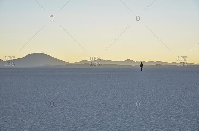 Bolivia- Salar de Uyuni- woman walking on salt lake at sunset