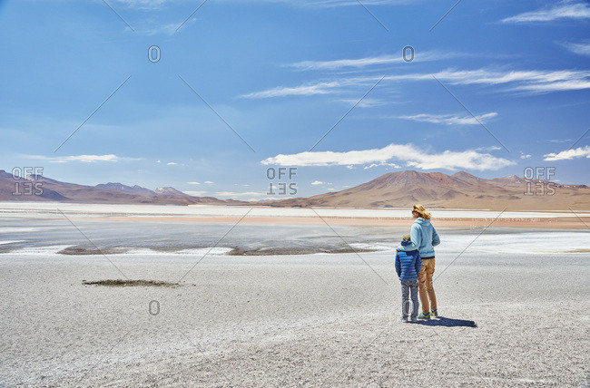 Bolivia- Laguna Colorada- mother and son at lakeshore with view to the Andes