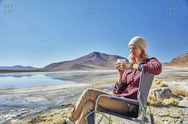 Bolivia- Laguna Colorada- woman sitting on camping chair at lakeshore drinking from cup