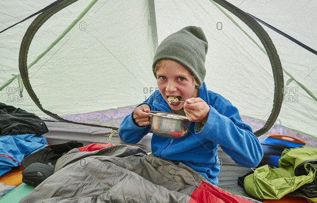 Bolivia- La Paz- boy eating from bowl in tent