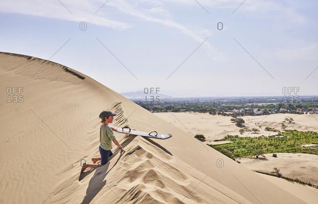 Peru- Ica- boy with sandboard on sand dune