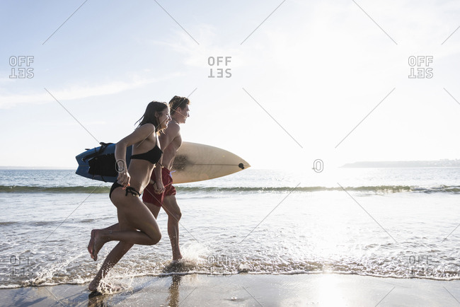 France- Brittany- young couple with surfboard running in the sea