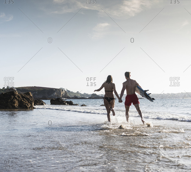 France- Brittany- young couple with surfboard running hand in hand in the sea