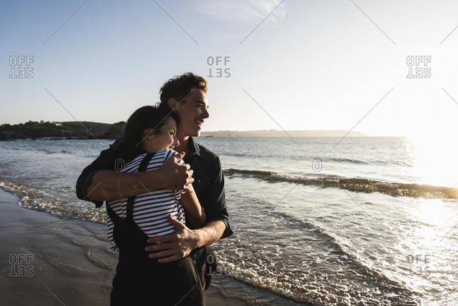 France- Brittany- happy young couple hugging on the beach at sunset