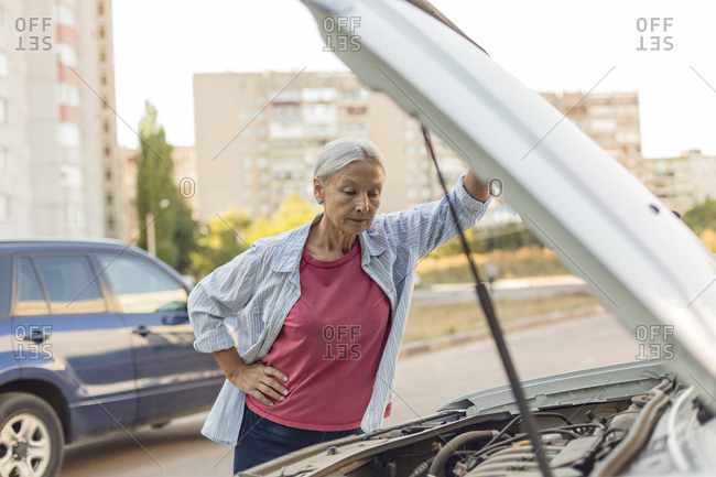 Senior woman looking at car engine