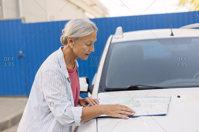 Senior woman looking at road map on  her car bonnet