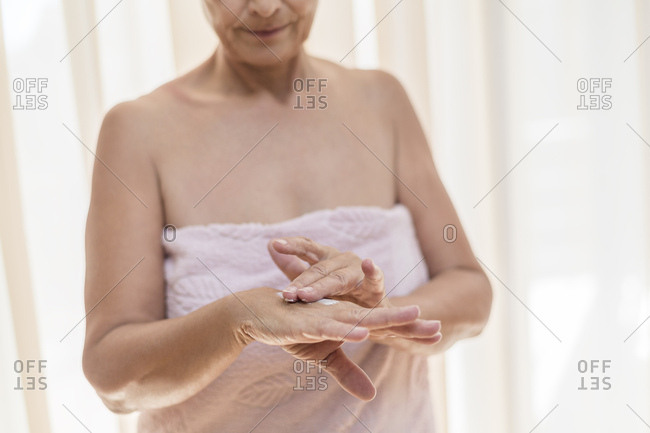 Senior woman applying cream on hand in the morning