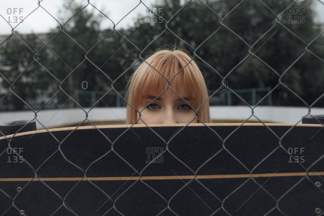Portrait of young woman behind carver skateboard and wire mesh fence
