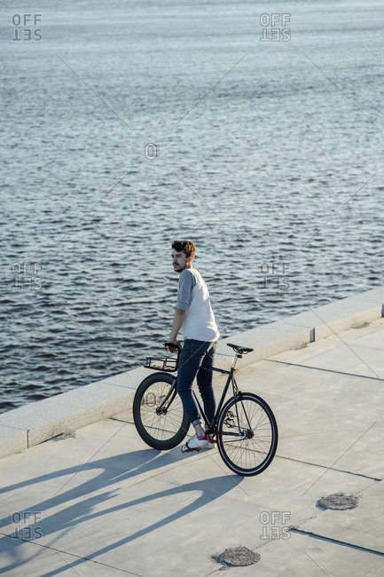 Young man with commuter fixie bike having a break at the riverside