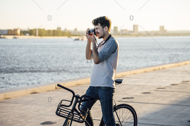 Young man with commuter fixie bike taking a picture at the riverside
