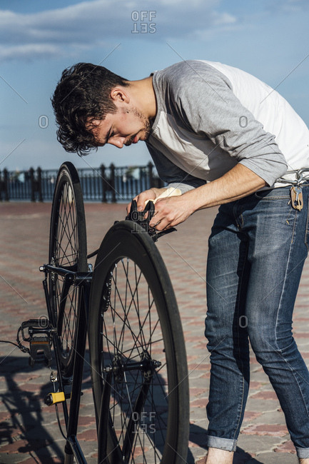 Young man repairing commuter fixie bike