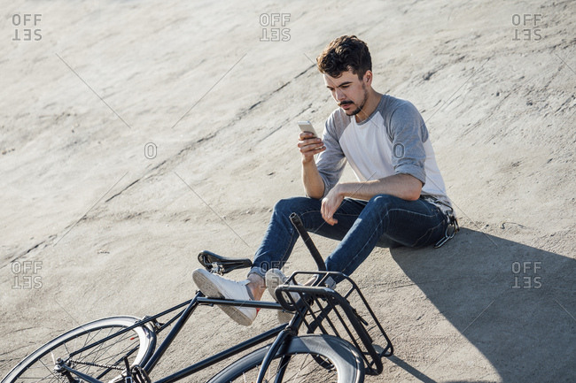 Young man with commuter fixie bike sitting on concrete wall using cell phone