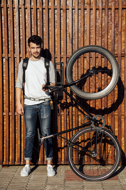 Portrait of young man with backpack holding commuter fixie bike