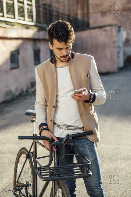 Young man with commuter fixie bike on a backyard in the city checking cell phone