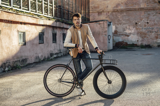 Young man with commuter fixie bike on a backyard in the city