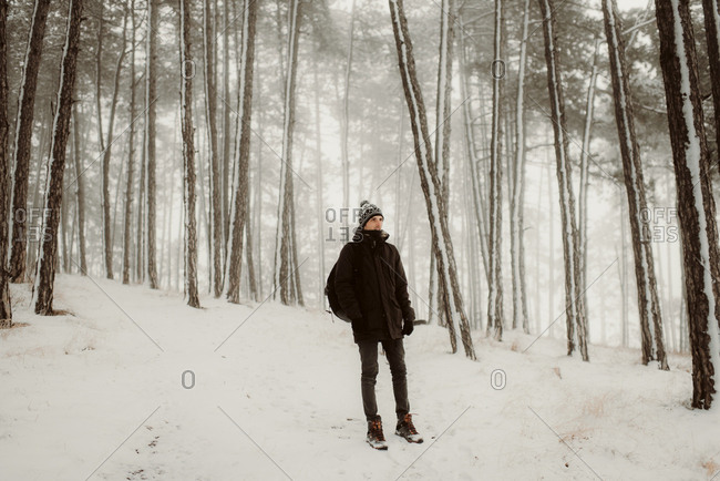 Person walking in fresh snow in a forest on a winter day