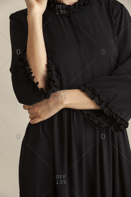 Detail shot of model in a studio wearing a black dress